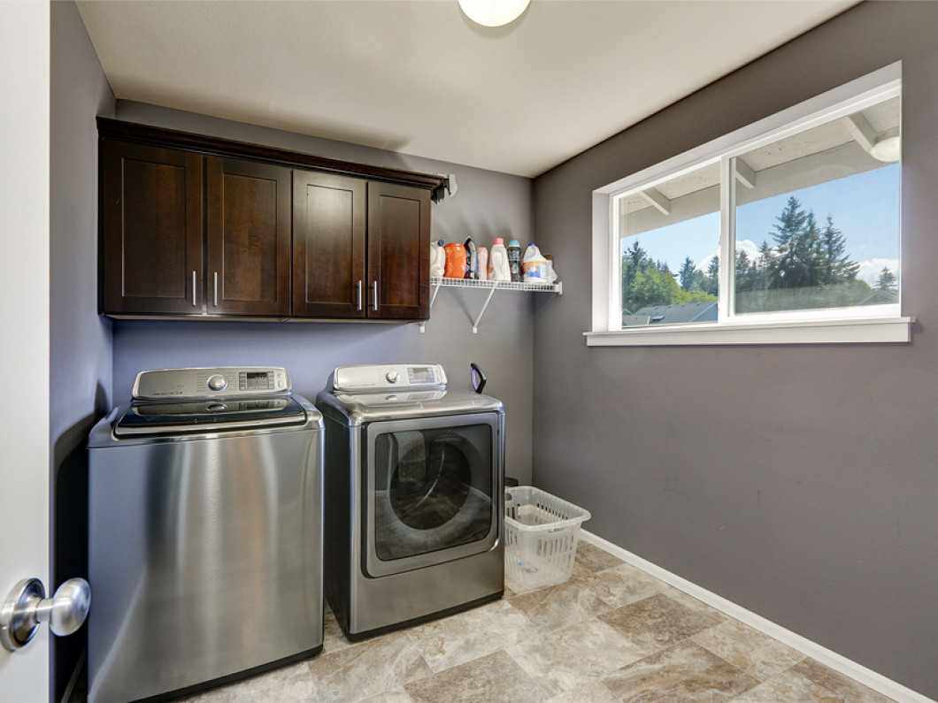 A stainless steel washing machine and dryer set in a laundry room