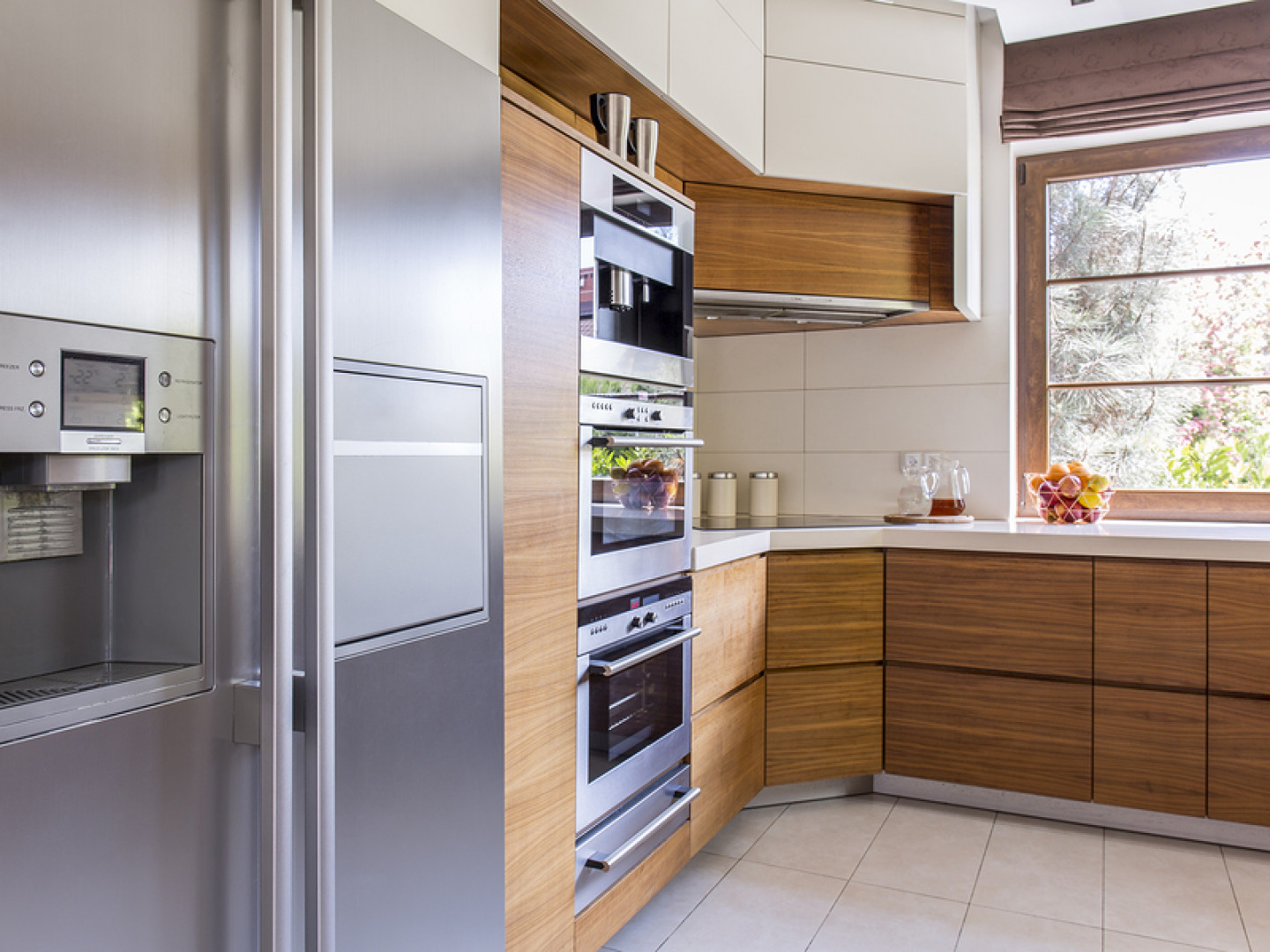 A stainless steel refrigerator with french doors and water and ice dispenser